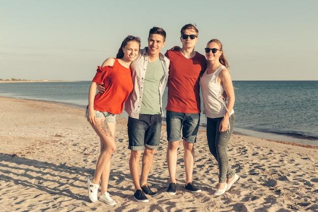 Grupo de jovens desfrutar de festa de verão na praia Foto Premium