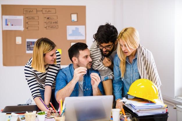Grupo de jovens designers criativos em cima de uma mesa falando sobre problemas no seu trabalho. Foto Premium