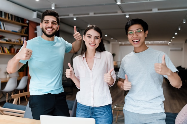 Grupo de jovens diversas pessoas sorrindo no escritório Foto Premium