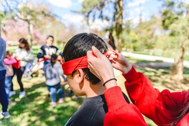 Grupo de jovens em uma escola ao ar livre jogando cobrir seus olhos com um véu vermelho para encontrar o parceiro Foto Premium