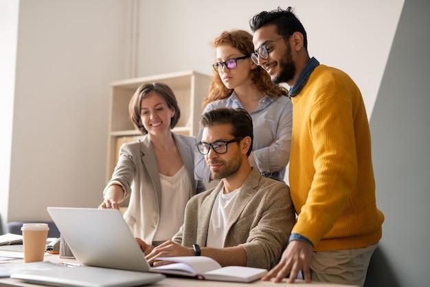 Grupo de jovens especialistas em negócios multiétnicos olhando para a tela do laptop e analisando a apresentação juntos no escritório Foto Premium