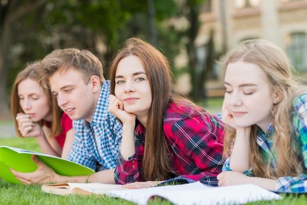Grupo de jovens estudantes aprendendo no parque Foto gratuita