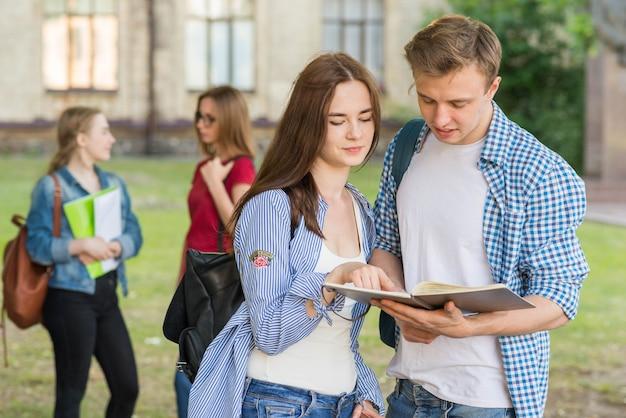 Grupo de jovens estudantes em frente ao prédio da escola Foto gratuita
