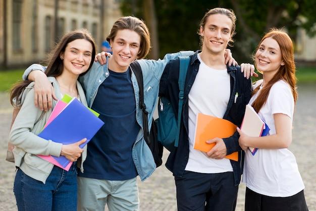 Grupo de jovens estudantes felizes em se reunir Foto gratuita