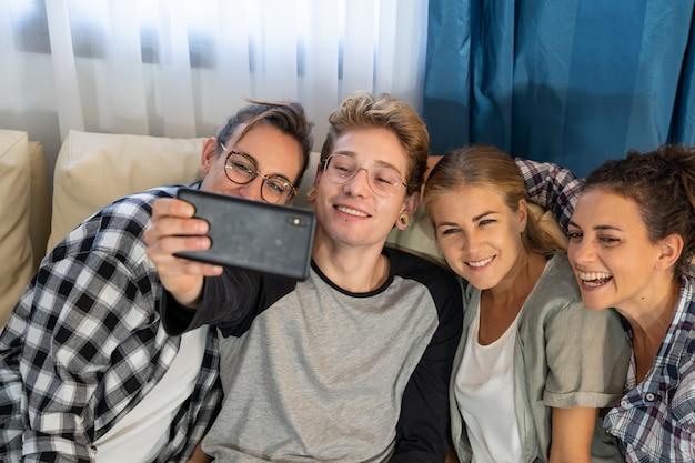 Grupo de jovens fazendo uma selfie, sentado em um sofá Foto gratuita