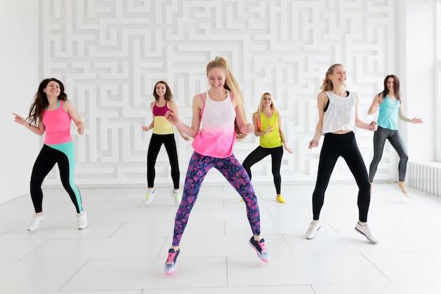 Grupo de jovens felizes no sportswear na aula de fitness dança no estúdio de fitness branco Foto Premium
