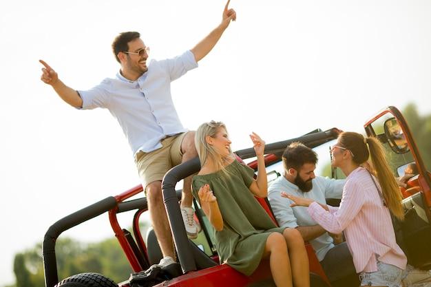 Grupo de jovens se divertindo de carro ao ar livre em dia quente de verão Foto Premium