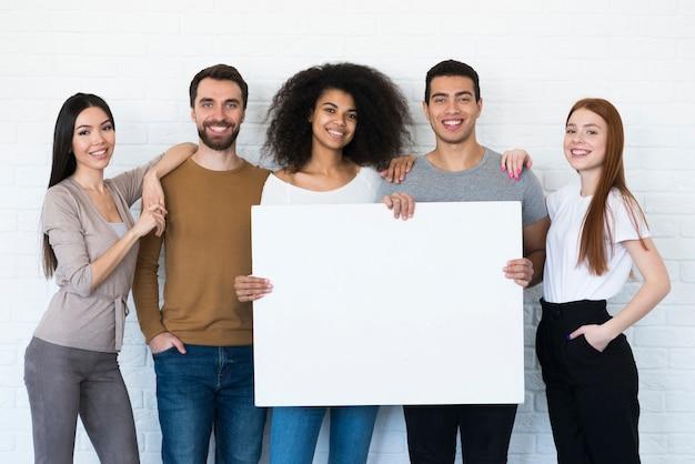 Grupo de jovens segurando um cartaz Foto gratuita