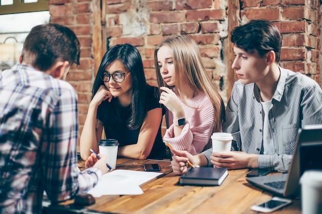 Grupo de jovens sentados em um café, bebendo café e discutindo novas idéias. Foto Premium