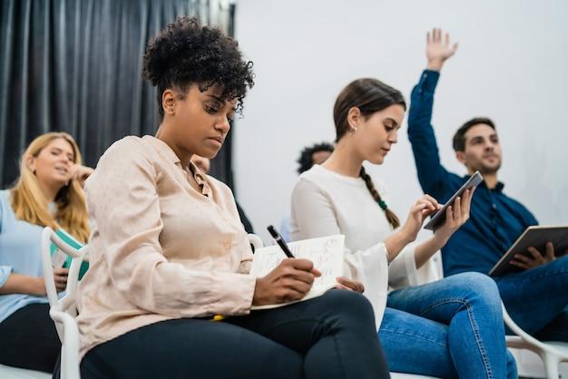 Grupo de jovens sentados na conferência enquanto levantam as mãos para fazer uma pergunta. conceito de treinamento de seminário reunião de equipe de negócios. Foto gratuita