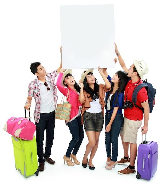 Grupo de jovens turistas segurar uma bandeira branca e olhar para cima Foto Premium