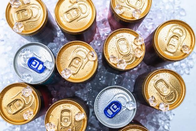 Grupo de latas de alumínio no gelo, bebida gelada. Foto Premium