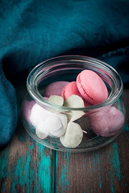 Grupo de macarons feitos de morangos, creme, chocolate e mirtilos. foto rústica. Foto Premium