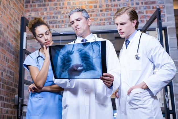 Grupo de médicos examinando relatório de machado no hospital Foto Premium