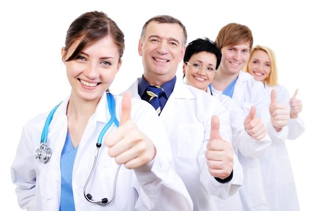 Grupo de médicos felizes e rindo com gestos de positivo em pé na fila Foto gratuita