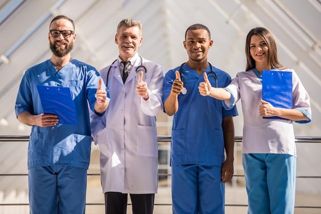 Grupo de médicos mostrando os polegares no hospital. Foto Premium