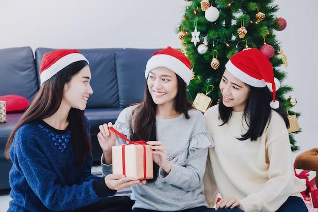 Grupo de mulher bonita asiática que guarda caixas de presente. rosto sorridente no quarto com decoração de árvore de natal para férias Foto Premium