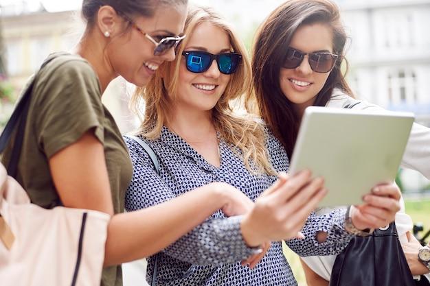 Grupo de mulheres elegantes curtindo a cidade e usando um tablet digital Foto gratuita