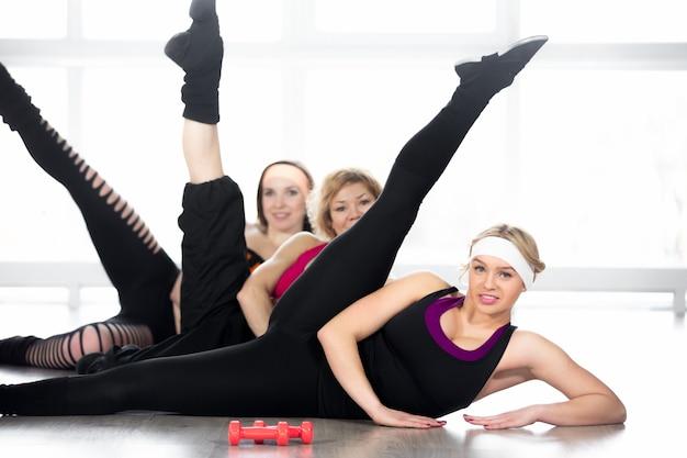 Grupo de mulheres fazendo exercícios aeróbicos em sala de aula Foto gratuita
