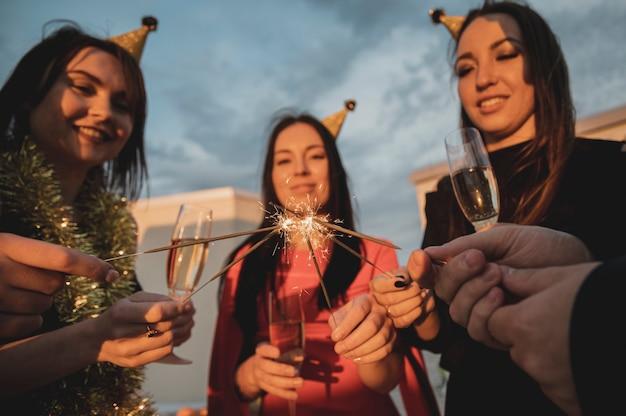 Grupo de mulheres festas, acendendo os estrelinhas Foto gratuita