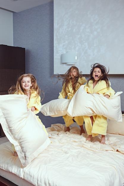 Grupo de namoradas se divertindo na cama. garotas de crianças rindo felizes brincando na cama branca no quarto. Foto gratuita