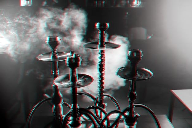 Grupo de narguilés no interior de uma sala de narguilé com fumaça Foto Premium