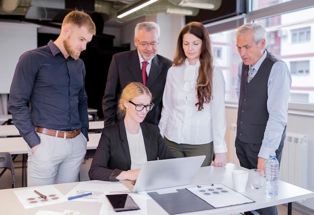 Grupo de parceiros de negócios olhando surpreendentemente na tela do laptop Foto gratuita