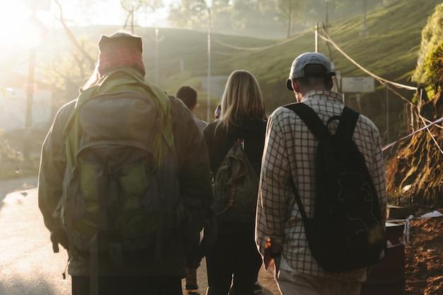 Grupo de pessoas caminhando pela estrada na luz solar bonita. closeup vista traseira Foto Premium
