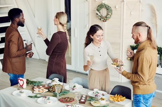 Grupo de pessoas celebrando o natal na sala de jantar Foto Premium