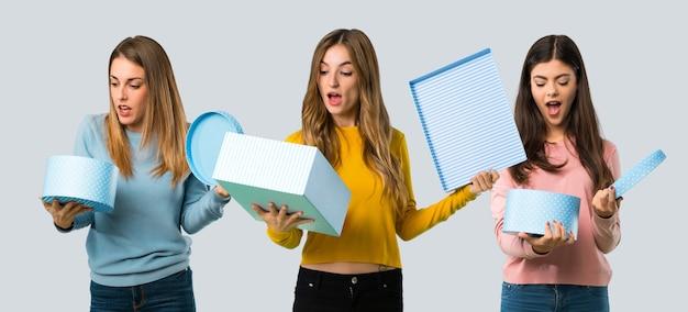 Grupo de pessoas com roupas coloridas, segurando a caixa de presente nas mãos em fundo colorido Foto Premium