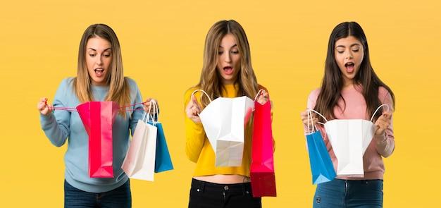 Grupo de pessoas com roupas coloridas surpreso, mantendo um monte de sacos de compras Foto Premium