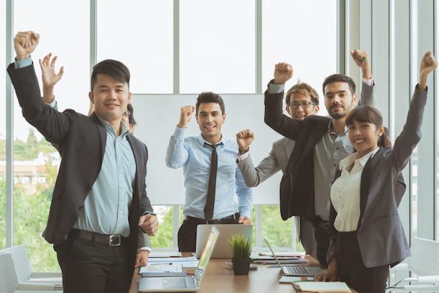 Grupo de pessoas de colega de negócios reunião em pé e mãos levantadas juntos pronto para trabalhar para o sucesso Foto Premium