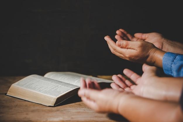 Grupo de pessoas de mãos dadas rezando adoração acreditam Foto gratuita