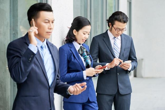 Grupo de pessoas de negócios étnicos usando seus telefones ao ar livre Foto gratuita