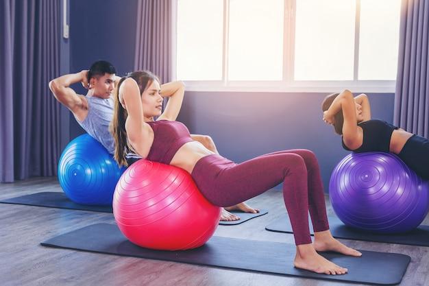 Grupo de pessoas em forma trabalhando na aula de pilates com bola de fitness Foto Premium
