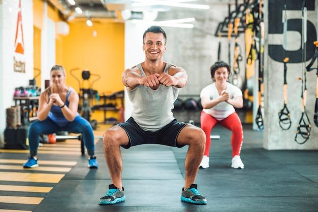 Grupo de pessoas fazendo exercício de aquecimento no clube de fitness Foto gratuita