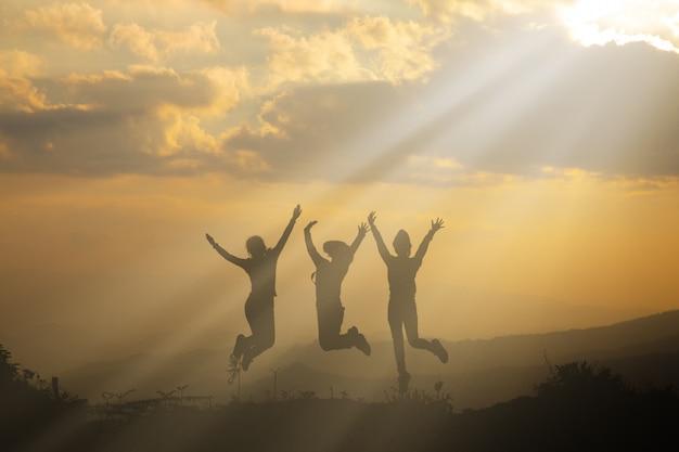 Grupo de pessoas felizes brincando no pôr do sol de verão na natureza Foto gratuita