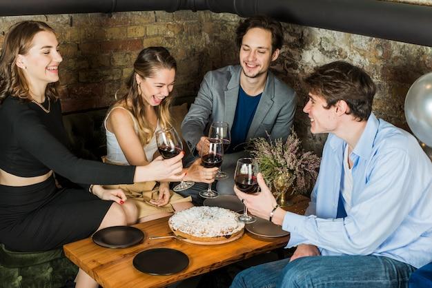 Grupo de pessoas felizes brindando na festa da noite Foto gratuita