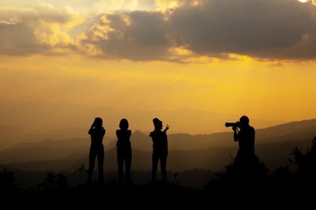 Grupo de pessoas felizes fotografando na montanha ao pôr do sol Foto gratuita