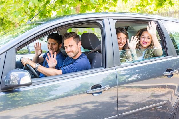 Grupo de pessoas no carro acenando as mãos Foto Premium