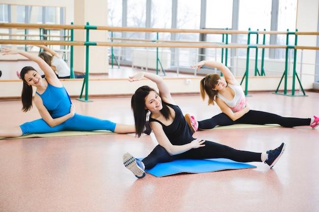 Grupo de pessoas no ginásio em uma aula de alongamento Foto Premium