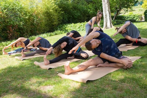 Grupo de pessoas praticando yoga e alongamento de corpos Foto gratuita