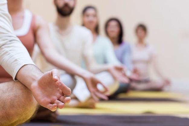 Grupo de pessoas que fazem a meditação na esteira do exercício Foto gratuita