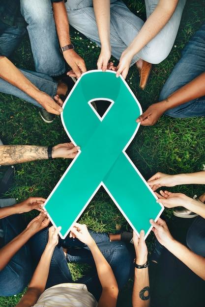 Grupo de pessoas segurando uma fita colorida verde Foto gratuita