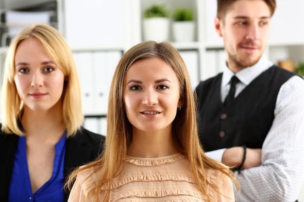 Grupo de pessoas sorridentes ficar no escritório olhando Foto Premium