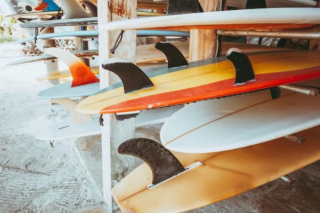 Grupo de placas de ressaca coloridas diferentes em uma pilha disponível para o aluguel na praia. Foto Premium