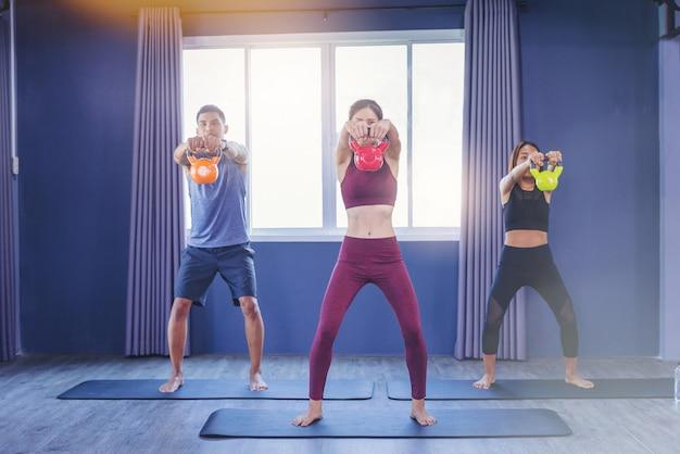 Grupo de povos aptos que guardam o sino da chaleira durante uma classe de exercício no gym da aptidão. Foto Premium