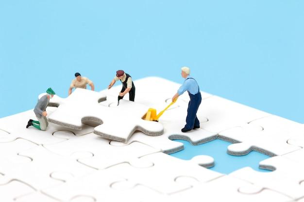 Grupo de povos diminutos que montam o enigma de serra de vaivém. conceito de trabalho em equipe de negócios. Foto Premium