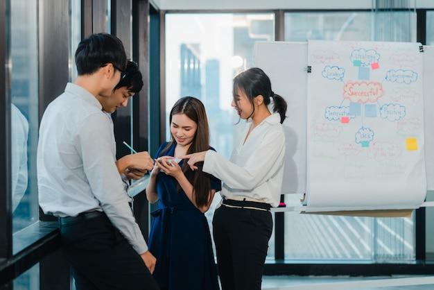 Grupo de processo colaborativo de empresários multiculturais em roupas casuais inteligentes se comunicando e usando a tecnologia enquanto trabalham juntos no escritório criativo. a equipe de jovens profissionais da ásia trabalha. Foto gratuita