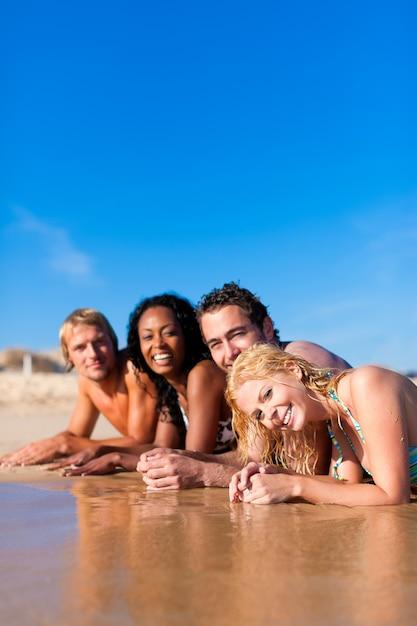 Grupo de quatro amigos - homens e mulheres - na praia com muita diversão em suas férias Foto Premium